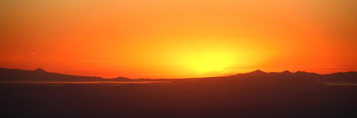 Foto auf AluDibond Rotglühen Panoramic View Of Silhouette Landscape Against Orange Sky During Sunset