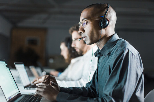 Side view of call center operator communicating with client. African American young man in eyeglasses typing on laptop while serving client. Call center concept