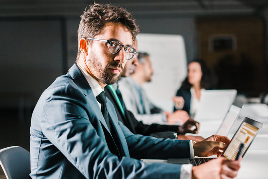 Side view of focused man in eyeglasses working in office. Serious handsome businessman sitting at table with laptop and looking at camera. Business, working late concept