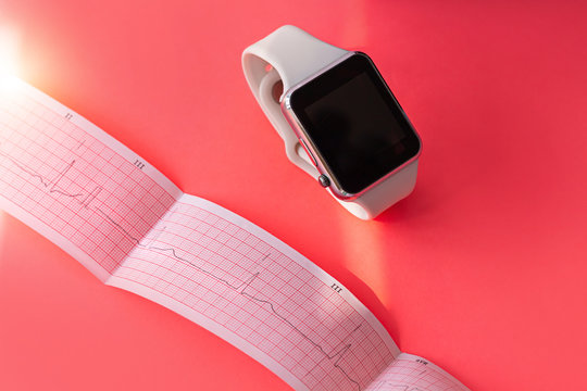 Smart watch on white sports silicone band, ECG diagram paper on pink coral background. Cardiogram medical examination. Prevent hearts disease, mitral valve prolapse syndrome.Analyze people heart rate.