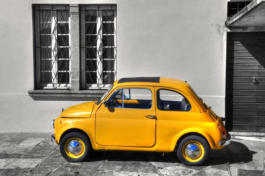 Beautiful picture of a yellow vintage car against a greyscale house