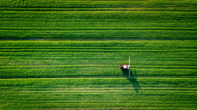 Straight lines field with a tractor spreading