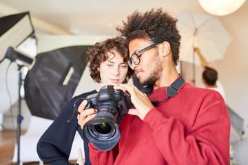Young photographer explains the reflex camera Fotobehang
