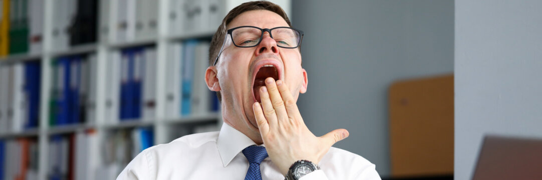 Tired businessman office sits at table and yawns