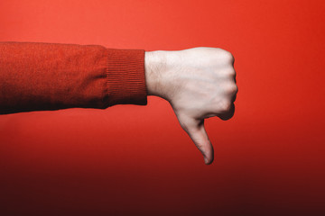 Man hand shows thumb down on red background.