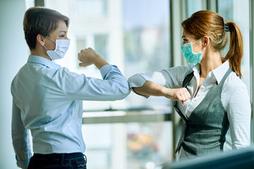 Female colleagues with face masks elbow bumping while greeting in the office.