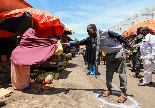 A Somali woman sells fruits to a customer standing at a social distancing signage, as a measure to stem the growing spread of the coronavirus disease (COVID-19) outbreak, at the market centre in Hamarweyne district in Mogadishu