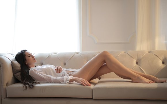 Attractive female sleeping on the couch wearing loungewear