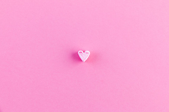 Pink background with one little heart. The concept of minimalism. Love card, Valentine's day, Mother's day, Birthday.