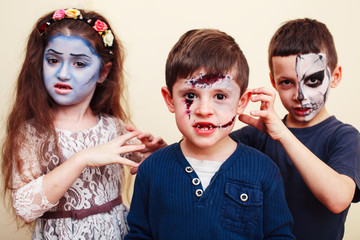 zombie apocalypse kids concept. Birthday party celebration facepaint on children dead bride, scar face, zombie skeleton together closeup makeup emotional posing. Wall mural