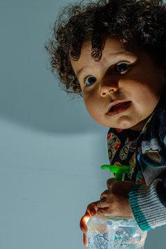 Bebê de 1 ano preparando a limpeza das mãos em combate ao corona virus, covid-19 durante a quarentena.
