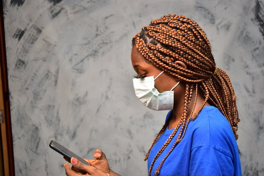 young black woman wearing a face mask making a phone call close up