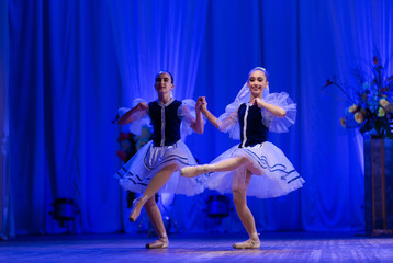 Young girls ballerina in a blue and white costume dancing ballet performance on stage in a theater