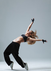young woman jumping on studio backdrop