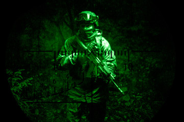 Portrait of a commando in the night sight of a sniper rifle. The concept of military operations, international conflicts, special forces.