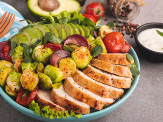 Fototapete - roasted sliced chicken fillet with brussels sprouts, avocado, tomatoes and herbs close up