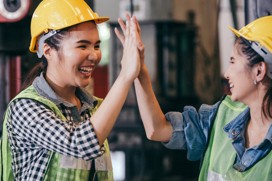 Happy cheerful female engineer or industrial technician worker giving high five to colleagues after work project success. woman wear protective hard hat in manufacturing factory. teamwork concept
