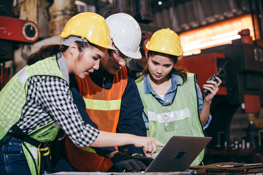 Asian engineer or technician man foreman training female trainee using program or system in industry manufacturing factory. teamwork and corporate people working hard in industrial construction site