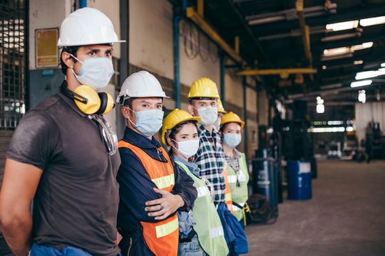 Group of industrial or engineer corporate workers wear protective mask and hard hat helmet standing line up and looking in same direction, industry manufacturing factory people  working with visions
