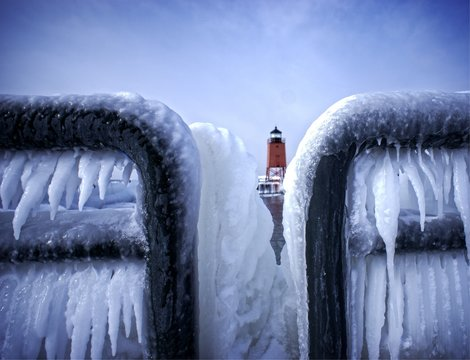 Close-up Of Frozen Railing Against Lighthouse