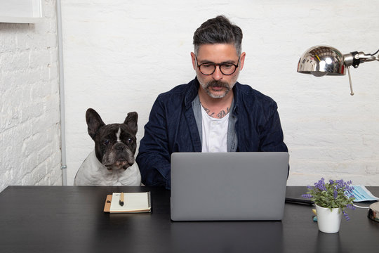 Man with glasses freelance working from home with his dog sitting together at workspace