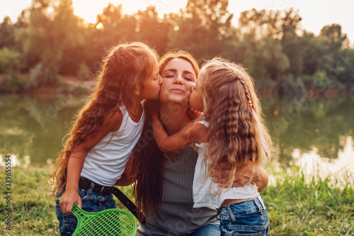 Mother's day. Kids kissing mother on cheek. Family walking by in spring park by lake after playing badminton.