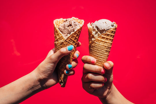 Two girls hands holding up ice cream cones against bright pink background