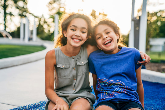Portrait of smiling sisters outside in park