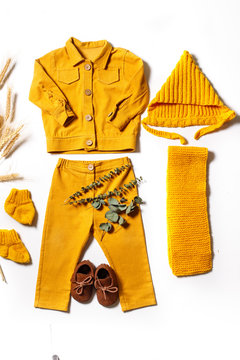 Flatlay of children's clothing in a rustic style. Stylish children's clothes. Knitted hat, shirt, trousers, scarf in yellow tones.the view from the top
