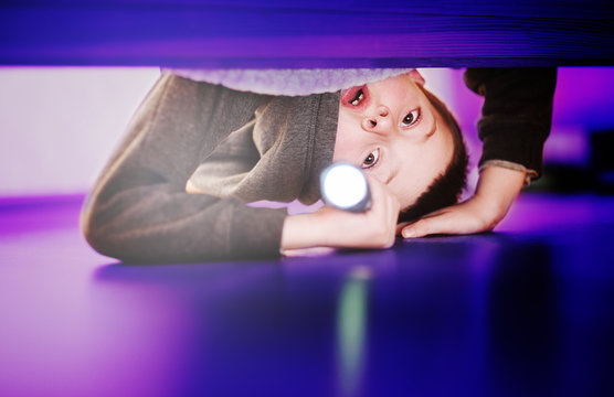 a scared little child boy looks under the bed with a flashlight on. Fear of the dark, children's fears.