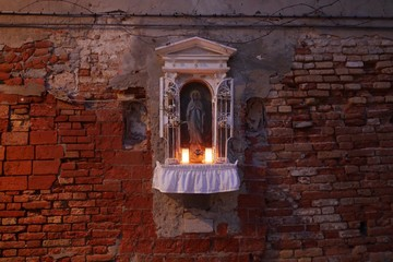 Illuminated Tea Light At Virgin Mary Altar On Brick Wall