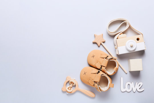 Set of baby shoes, toys and accessories on grey background. Newborn stuff. Flat lay, top view