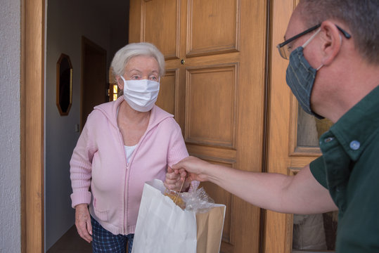 Senior woman with face mask gets neighborhood shopping assistance