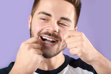 Fotomurales - Young man flossing teeth on color background