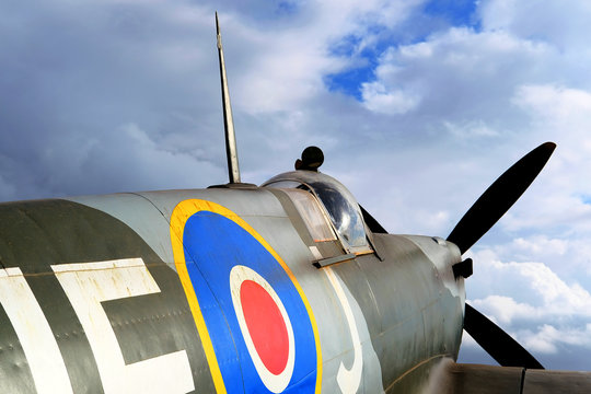 Angled view from the fuselage of a WW2 Spitfire Fighter Aircraft facing a cloudy sky background.