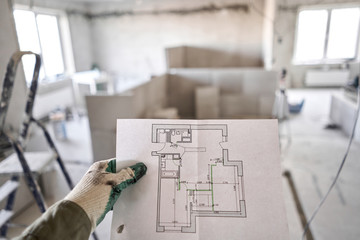 The construction worker hold in hands Architectural blueprints. Repair or construction of a new apartment. Concept for new house design or home improvement. Development of the apartment project. Wall mural