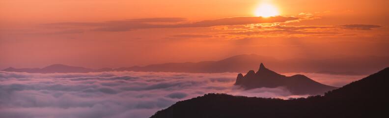 Fotobehang Koraal Mountains in the fog