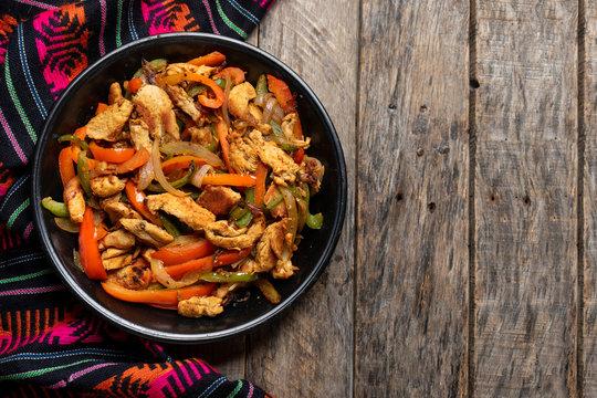 Mexican chicken fajitas on wooden background