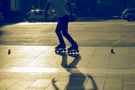 Low Section Of Man Roller Skating On Road At Sunset