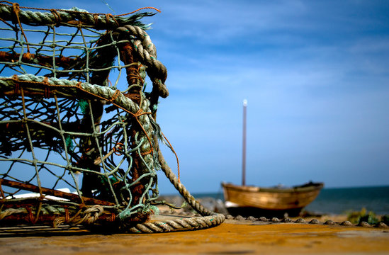 Close-up Of Lobster Trap On Pier Against Sky