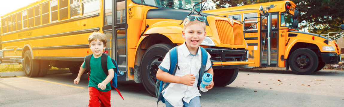 Two funny happy Caucasian boys students kids running near yellow bus on 1 September day. Education back to school. Children ready to learn, study. Web banner header for a website.