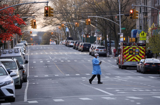 A medical worker crosses a road to return to Maimonides Medical Center after a break during the outbreak of the coronavirus disease (COVID19) in the Brooklyn borough of New York