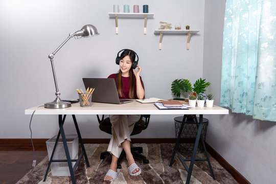A young, beautiful relaxing business asian girl use a laptop working remotely from home on desk as a freelancer, quarantine for Coronavirus and smart working concept.