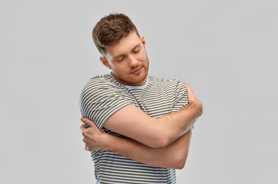 self loving, care and people concept - happy young man in striped t-shirt hugging himself over grey background