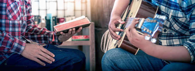 Worship God of two young christian sitting and sing a song, focus at hand, Christian worship concept.