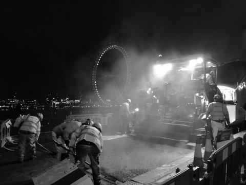 Workers Putting Asphalt On Street With Steamroller Against Millennium Wheel