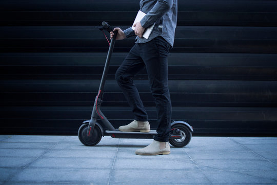 Shot of unrecognizable business person with tablet computer on his electric scooter commuting vehicle.