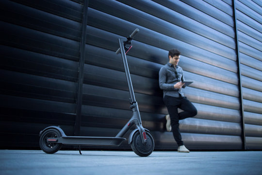 Electric scooter. Eco friendly modern way of transportation. In background handsome business person caucasian man using tablet computer leaning on black business building.