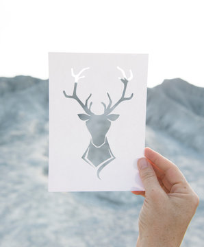 Hand holding perforated paper moose art with mountain background