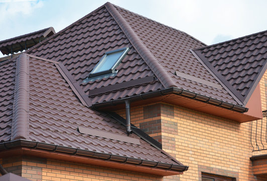 Complex roof design, metal tiled expensive roofing construction with a skylight, snow guards, chimney of a brick house.